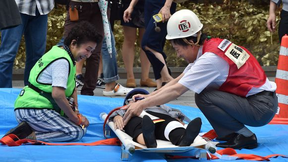 Mensen leren op straat eerste hulp te verlenen tijdens een 'drilsessie' in Tokio ter voorbereiding op de aardbeving.