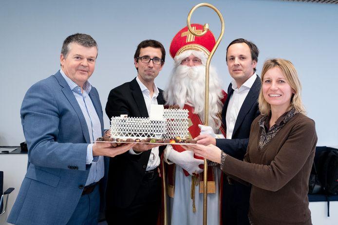 Sinterklaas schenkt een maquette- overgoten met een laag chocolade - aan burgemeester Bart Somers en schepen van Stadsontwikkeling Greet Geypen.