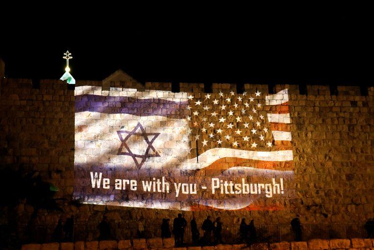 Een afbeelding van een Israëlische vlag en een Amerikaanse vlag met de woorden 'We are with you - Pittsburgh' wordt geprojecteerd op de muren van de Oude Stad in Jeruzalem.  Beeld REUTERS