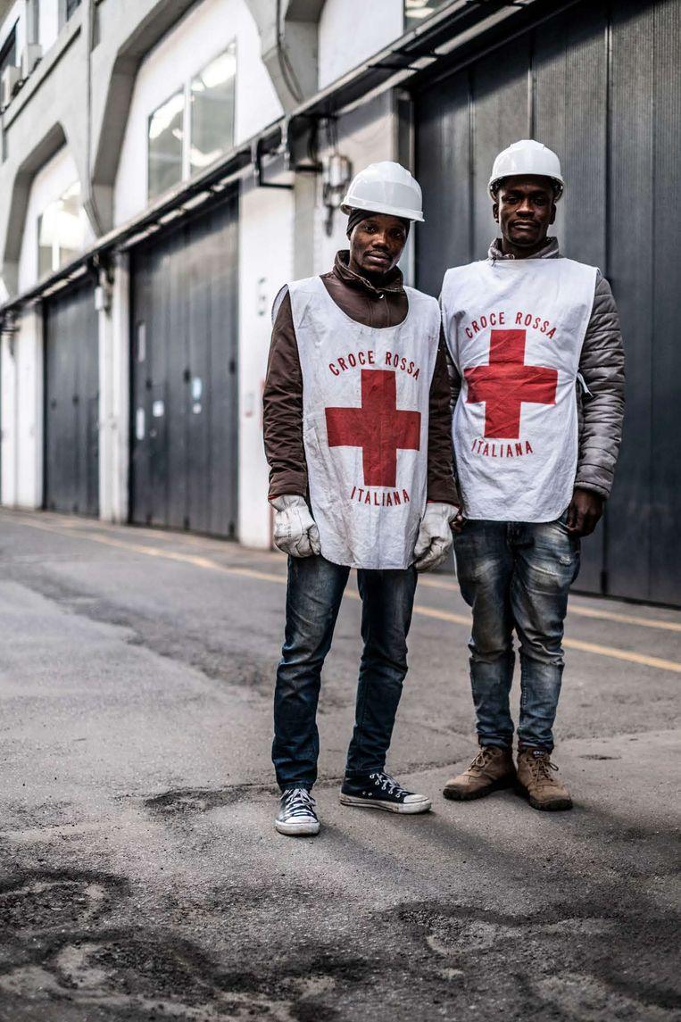 Seydou Ballu (l) en Youssouf Ouedraogo werken als vrijwilliger voor het Rode Kruis, dat voor de opslag van spullen zorgt van bewoners die hun woning verloren.  Beeld JONAS LAMPENS