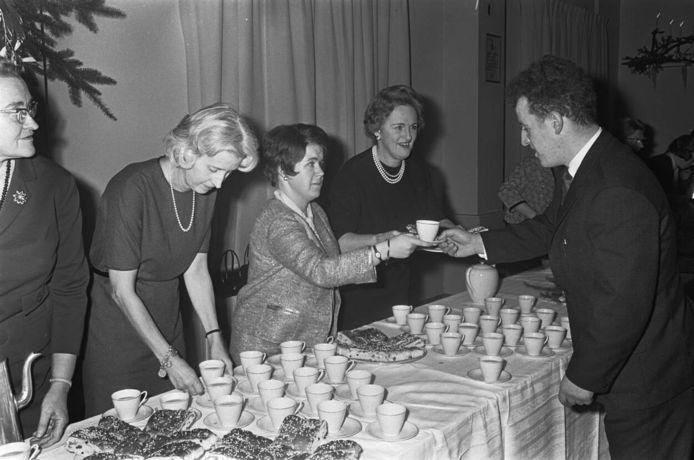 Prinses Christina geeft een personeelslid een kop chocolademelk tijdens de kerstviering op Paleis Soestdijk, 1966.