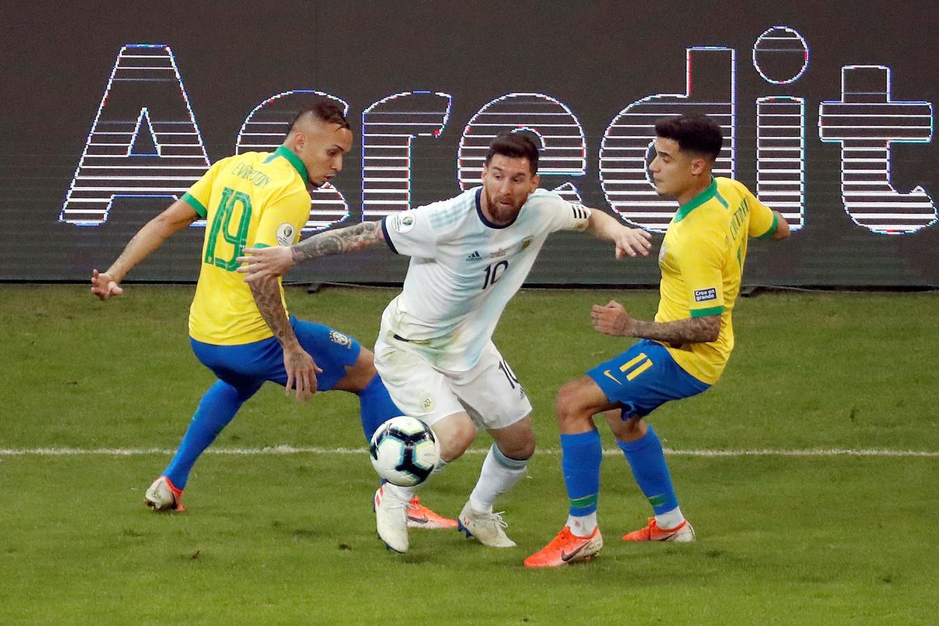 Everton Soares (L) probeert met Philippe Coutinho (R) Lionel Messi af te stoppen.