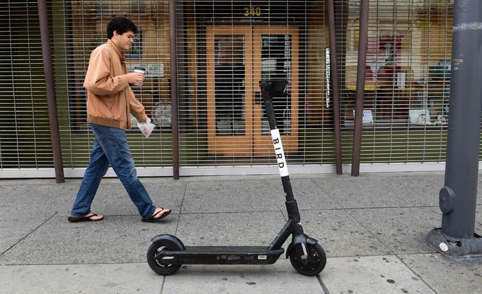 A man walks past a Bird scooter on a Los Angeles sidewalk on March 19, 2020. - Electric scooter companies Bird and Lime have suspended services across North America for an indefinite period amid the coronavirus epidemic and a drop in user numbers. (Photo by Frederic J. BROWN / AFP)