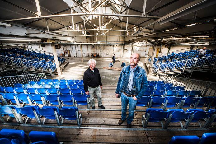 Benno Elkink (rechts) en tekstschrijver Jan Hofmeijer met op de achtergrond enkele koorleden die bezig zijn met geluidsdempende schermen in de voormalige fabriekshal waar de productie 'Rooje Roozen' wordt opgevoerd.