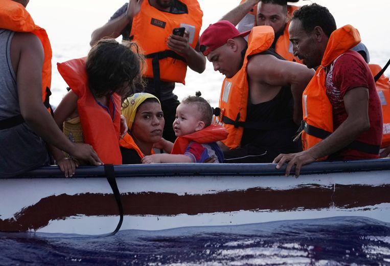Migranten op een houten boot richting Lampedusa op 28 augustus 2021. Beeld Reuters