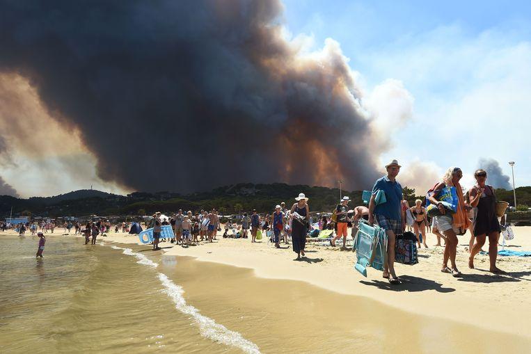Badgasten verlaten het strand bij de Franse plaats Bormes-les-Mimosas vanwege overlast door de bosbranden in de omgevin Beeld AFP