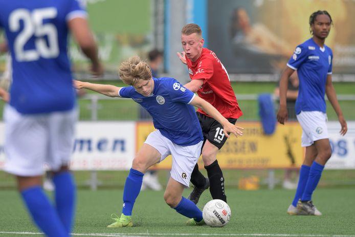 Proefspeler Wout Neelen, aan de bal voor FC Den Bosch, wordt fel op de huid gezeten door Iain Brands van Nivo Sparta.