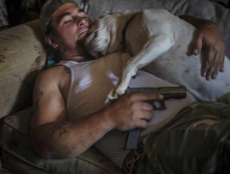 Militieleider Danny Bollinger (43) rust uit op zijn bank met pitbull en pistool.  Beeld © Espen Rasmussen/Verdens Gang/Panos Pictures