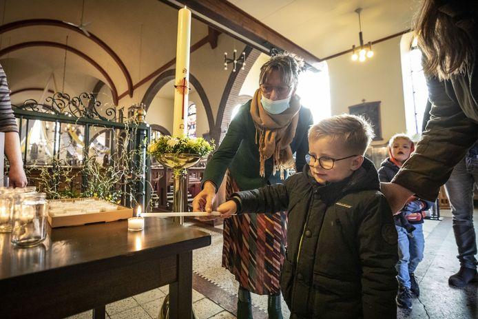 Mike Borghuis steekt in de Plechelmuskerk in De Lutte zijn kaarsje aan met vuur van de paaskaars. Thuis gaat hij er een paasvuurtje mee maken.