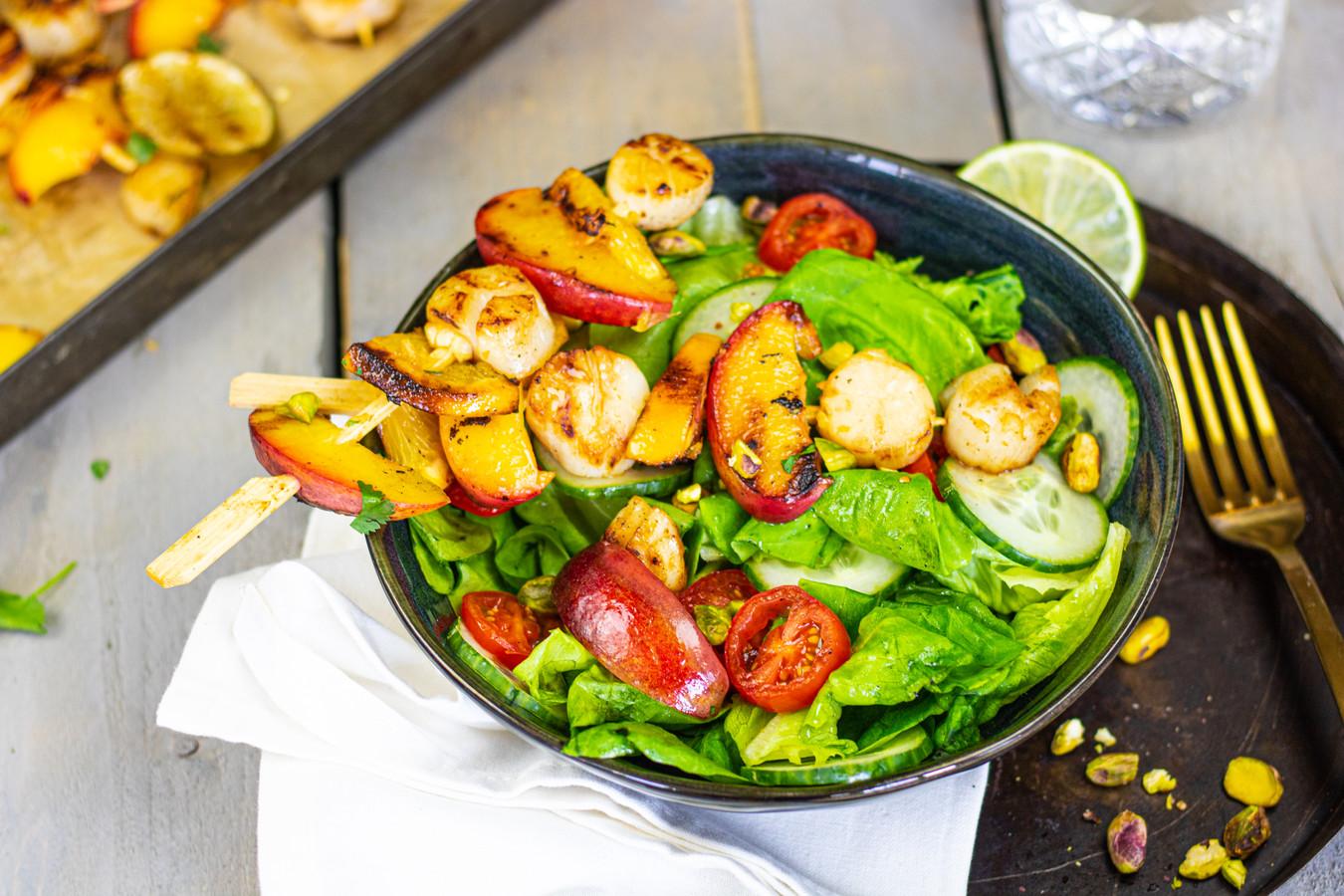 Salade met gegrilde coquilles, nectarine en pistachenoten