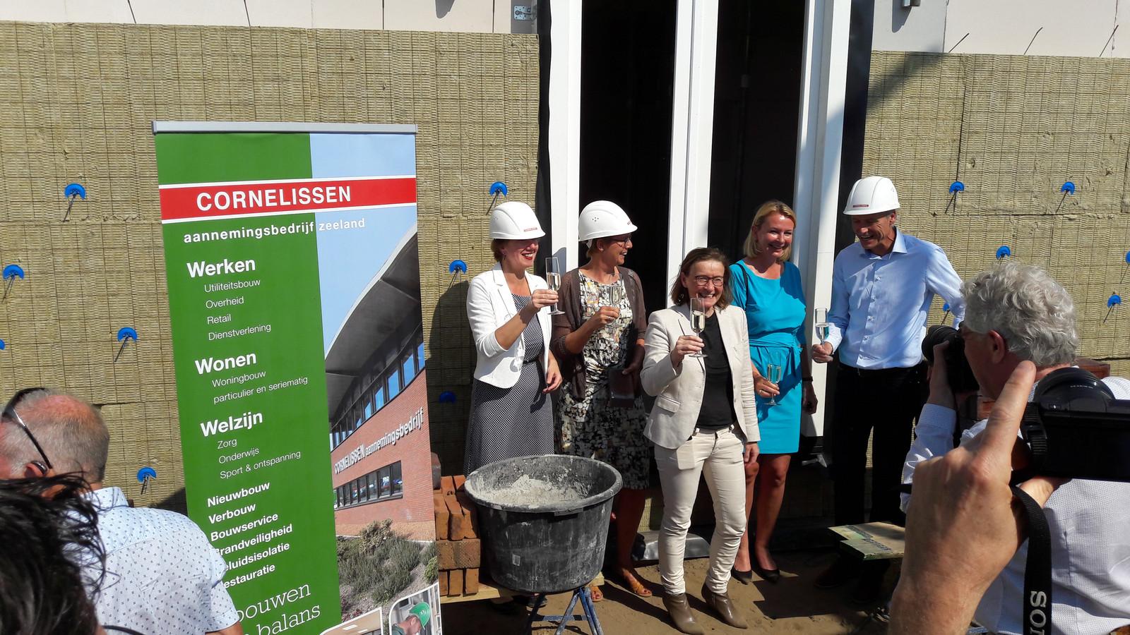 Wethouder Margo Mulder, Geke Haasjes, Clasien Schakenraad, Annemieke Bambach en Evert de Groot heffen het glas bij het Gastenhuis in aanbouw.