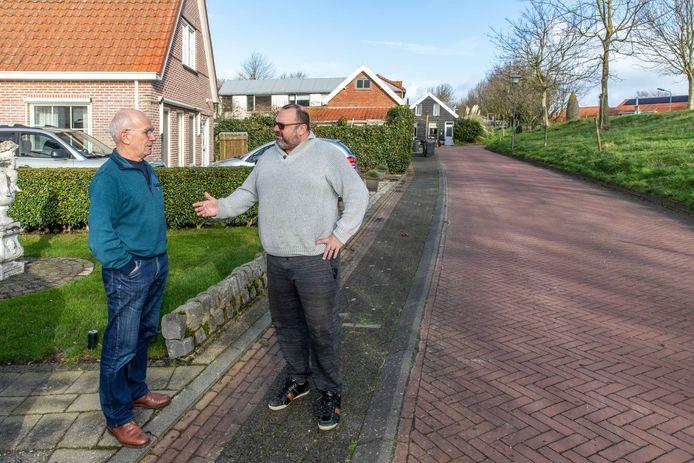 Danny de Groen (r) en buurman Dick Willebrands op het gewraakte stukje grond voor hun huis.