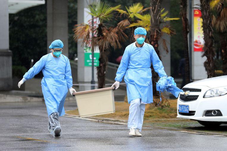 Verplegers in een ziekenhuis in de Chinese miljoenenstad Wuhan, waar patiënten liggen die besmet zijn geraakt met het nieuwe type coronavirus. Beeld REUTERS