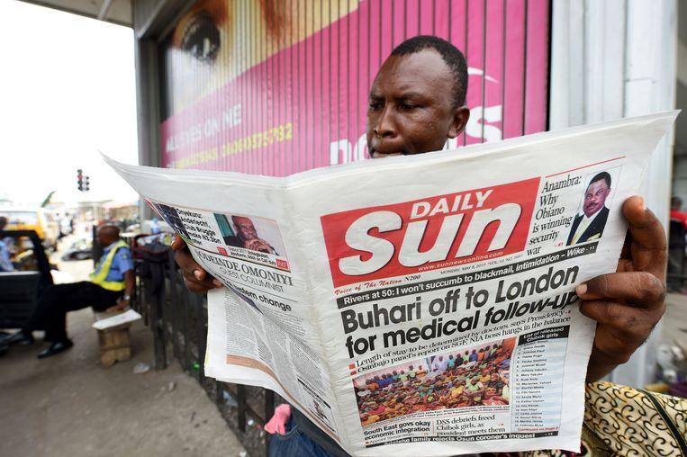 Een man leest in de krant over de gezondheidstoestand van president Buhari. Beeld AFP