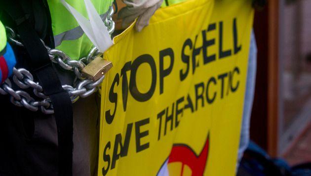 Actievoerders van Greenpeace bezetten de ingang van het hoofdkantoor van Shell. Activisten van de milieuorganisatie protesteren tegen proefboringen van de oliegigant in het Noordpoolgebied.