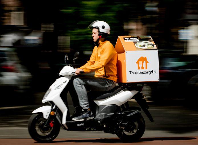 Een bezorger van Thuisbezorgd.nl verwerkt een bestelling.