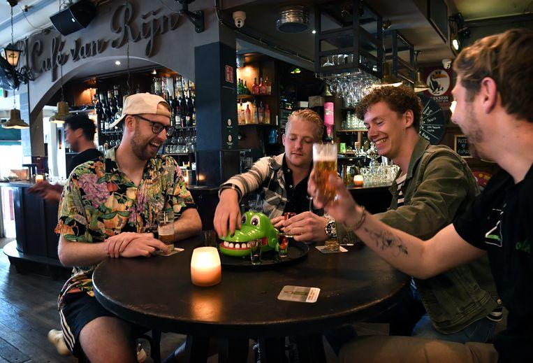 De kroeg is weer open. In café Van Rijn doen vier Nijmeegse studenten een drankspelletje. Beeld Marcel van den Bergh / de Volkskrant