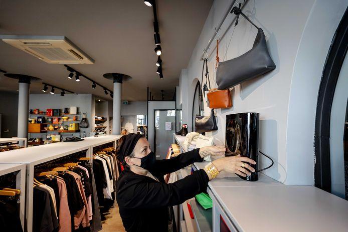 Een medewerker van een modewinkel aan het werk. Winkeliers zijn blij dat ze door de versoepelingen binnenkort weer zonder afspraak klanten mogen ontvangen.