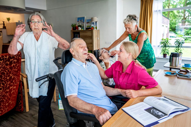 Bij woonzorgcentrum Het Spijk in Eefde probeert verpleegkundige Traci Schumaker (rechts) contact te maken met een van de bewoners. In dit verzorgingshuis werkt men nauwelijks meer met mondkapjes.  Beeld Raymond Rutting / de Volkskrant