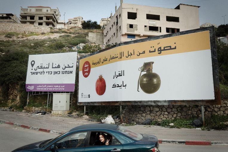 Reclameborden met opschriften in het Arabisch en Hebreeuws in de straten van Umm al-Fahm.  Beeld Daniel Rosenthal