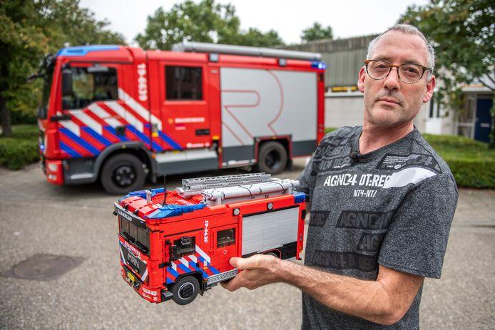 Patrick Pieters toont vol trots de door hem in detail, van Lego-blokjes nagebouwde nieuwe tankautospuit van de post Zaamslag die op de achtergrond staat.