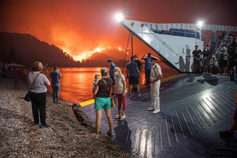 Bewoners van het Griekse eiland Evia werpen nog een blik op de branden, voordat ze aan boord gaan van een veerboot die ze in veiligheid brengt. Beeld NurPhoto via Getty