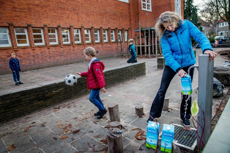 Een paar keer per dag komen bewoners met hun pakken en flessen naar een pomp aan het Wognumerplantsoen in Nieuwendam. Ze tappen daar water om te drinken en hun eten mee te koken. Beeld Jean-Pierre Jans