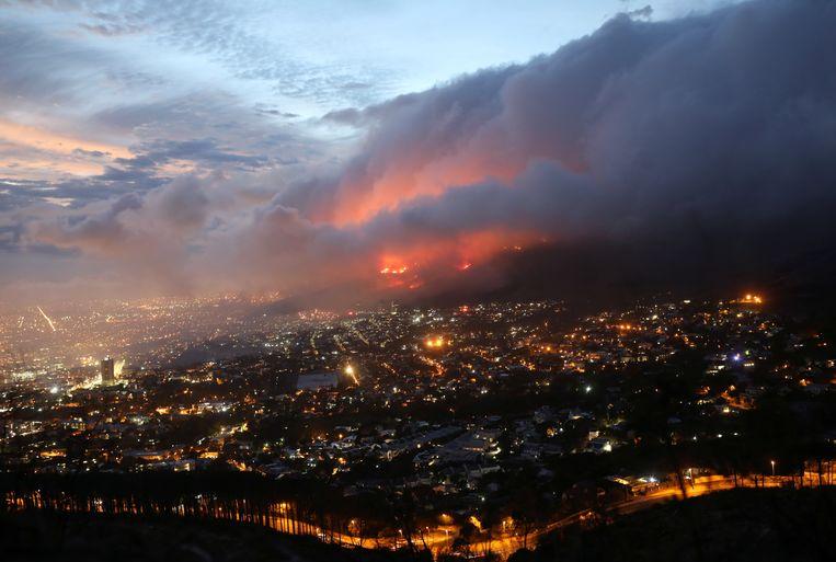 Gezicht op de flanken van de Tafelberg in Kaapstad, Zuid-Afrika, waar zondagochtend een hevige brand is uitgebroken. Delen van de Universiteit van Kaapstad zijn zwaar beschadigd. Het vuur komt steeds dichter bij de stad, aangewakkerd door de stevige wind. De brandweer zegt nog minimaal drie dagen nodig te hebben om de brand onder controle te krijgen.  Beeld Reuters
