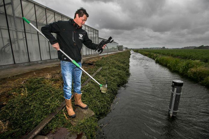 Een medewerker van het Hoogheemraadschap van Delfland meet de waterkwaliteit.