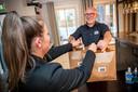 Fred Schel van brasserie 't Oude Raadhuis geeft een klant twee tassen met eten mee.