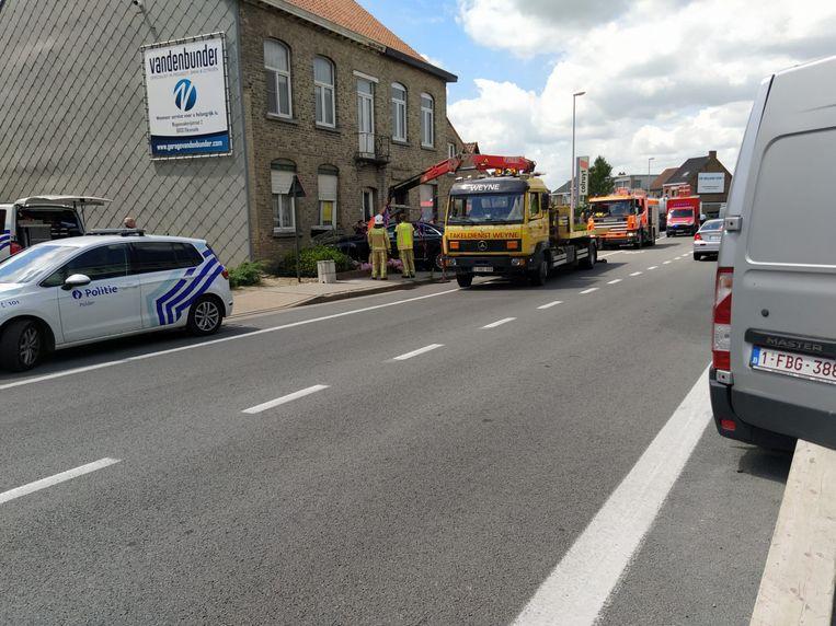 De wagen wordt getakeld. De brandweer moet de gevel stutten.