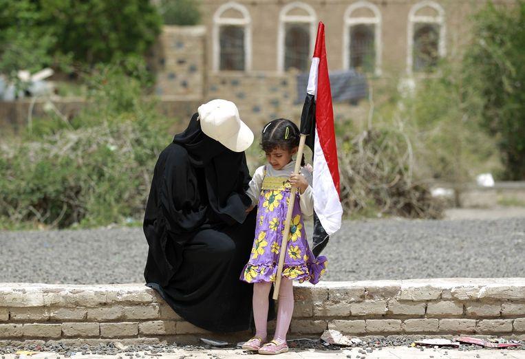 Een Jemenitische vrouw en kind houden een vlag vast tijdens een protest tegen de luchtaanvallen. Beeld afp