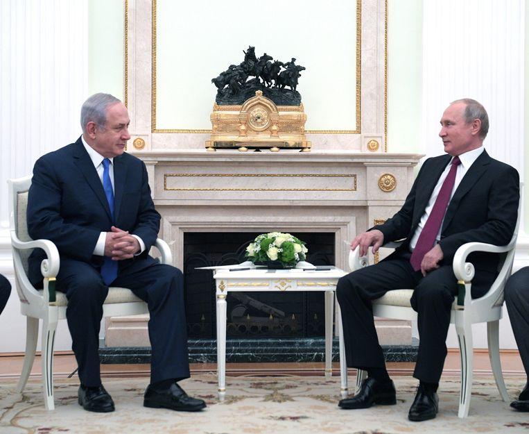 De Russische president Vladimir Poetin (R) praat met de Israëlische premier Benjamin Netanyahu (L) over het conflict in Syrië. Beeld EPA