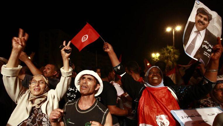 Demonstranten in de Tunesische hoofdstad houden een portret omhoog van de vermoorde politicus Mohammed Brahmi. Beeld null