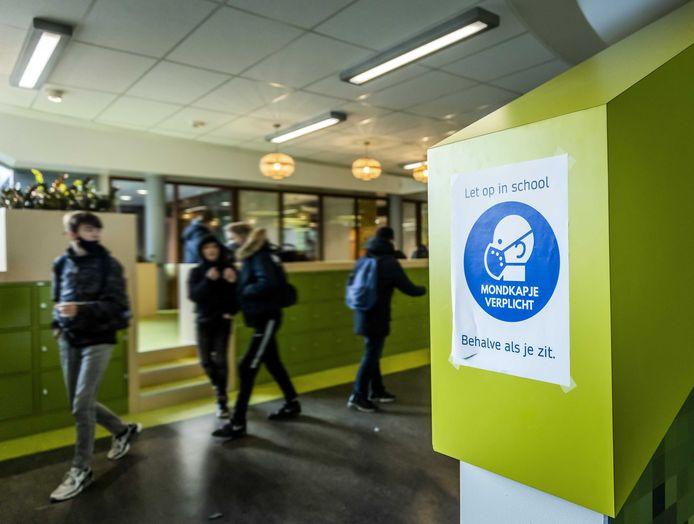 Leerlingen van een middelbare school dragen mondkapjes in de gangen.