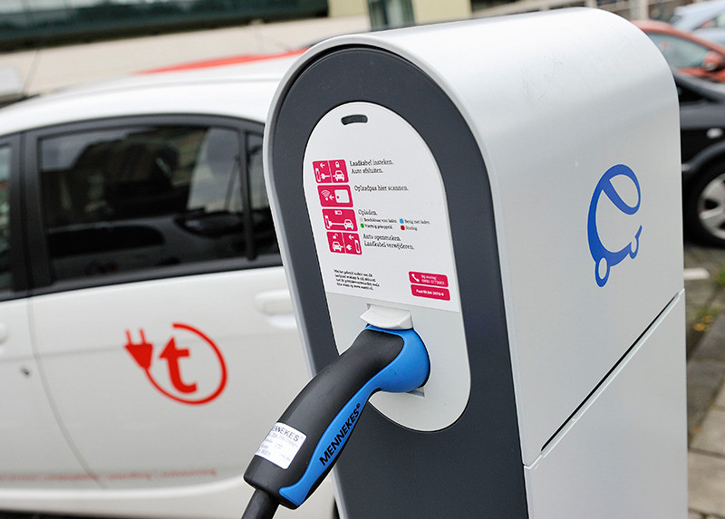 Een elektrische auto wordt opgeladen bij een oplaadpunt.
