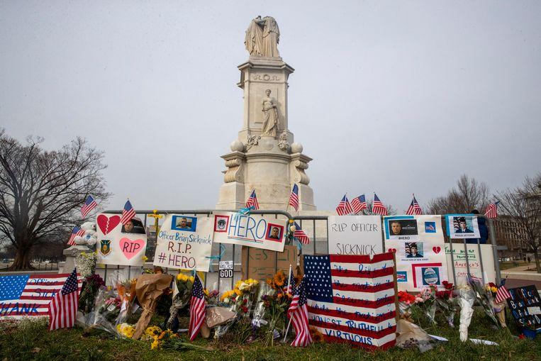 Bloemen en vlaggen voor de Capitool-agent die om het leven kwam bij de bestorming. Beeld EPA