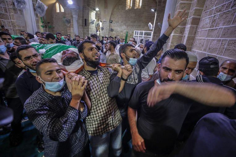 Palestijnen tijdens een begrafenis voor vijftien slachtoffers van een Israëlische luchtaanval in Gaza.  Beeld EPA