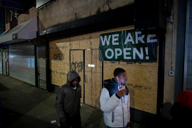 Twee mannen lopen in Philadelphia langs een winkel die is dichtgetimmerd met spaanplaat. Beeld Getty Images