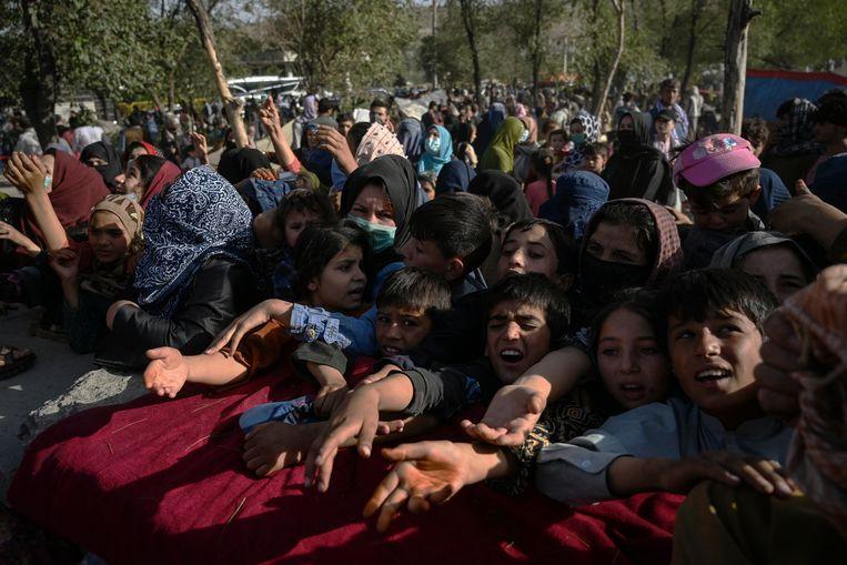 Voedseluitdeling voor Afghaanse families in de hoofdstad Kabul. Ze zijn gevlucht voor de gevechten  tussen de regeringstroepen en de Taliban, die steeds meer gebieden in handen krijgen. Beeld AFP