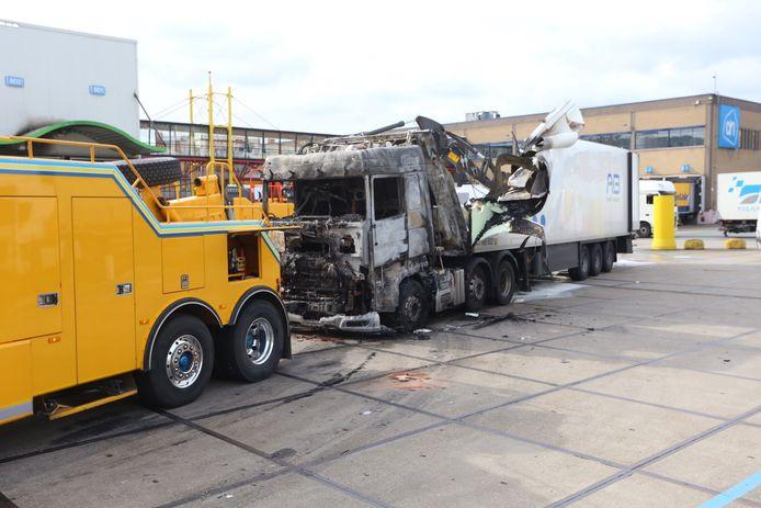 De berging van de uitgebrande vrachtwagen is een flinke klus. Een bergingsbedrijf is er al geruime tijd doende mee.