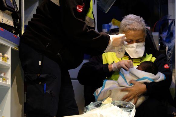 Reddingswerkers ontfermen zich over de baby.