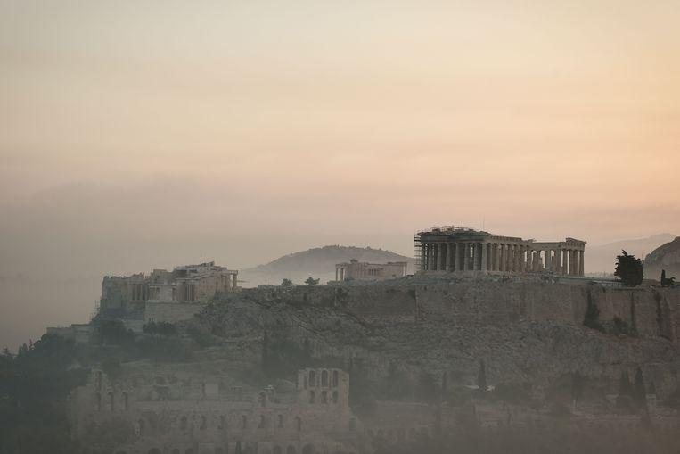 De Akropolis en het centrum van Athene gaan gesluierd onder dichte rookwolken vanwege branden aan de voet van de Parnithaberg, zo'n 30 kilometer van de Griekse hoofdstad vandaan.  Beeld AFP