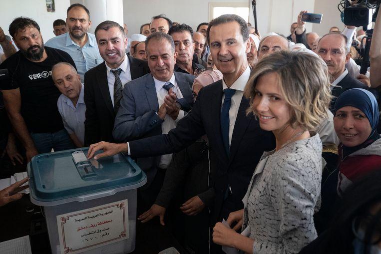 De Syrische president Bashar al-Assad en zijn vrouw Asma brengen hun stem uit. Beeld AP