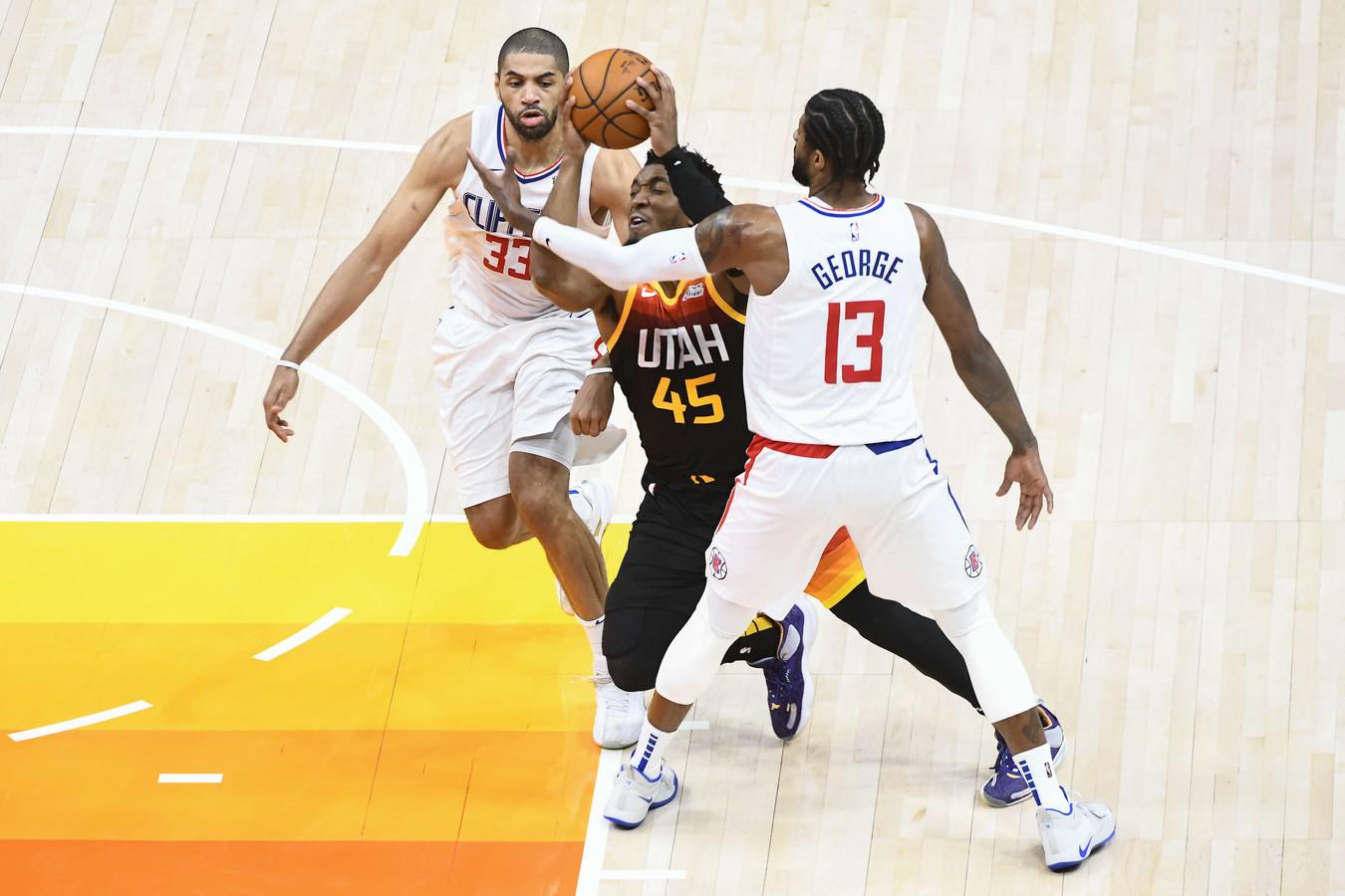 Donovan Mitchell van Utah Jazz tussen Paul George en Nicolas Batum van LA Clippers.