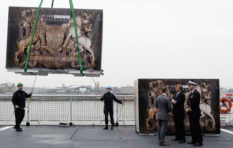 Wim Pijbes ziet in 2012 met toen nog Prins Willem-Alexander en vice-admiraal Matthieu Borsboom hoe een 17de-eeuwse spiegelversiering op transport gaat naar Greenwich voor een tentoonstelling aldaar. Beeld ANP