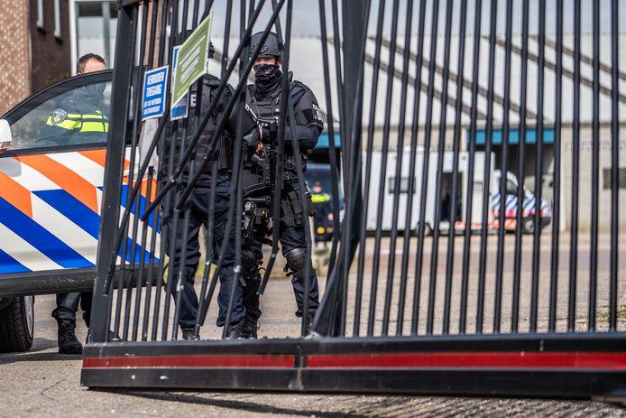 Zwaarbewapende agenten bewaken de loods.
