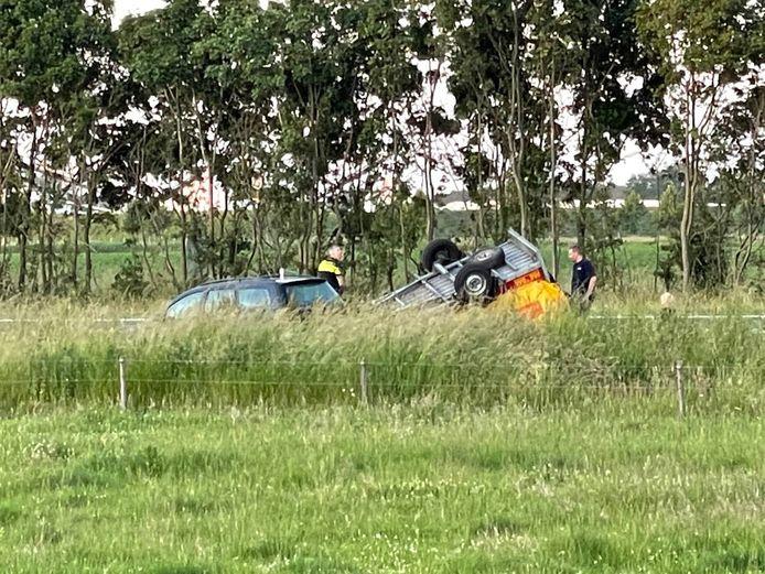 De auto met aanhanger raakte van de weg, waarna de aanhanger op de kop in de berm belandde.