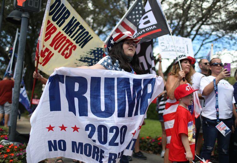 Mensen tonen hun steun voor voormalig president Donald Trump buiten het Hyatt Regency, waar de conservatieve politieke actieconferentie wordt gehouden op 27 februari 2021 in Orlando, Florida.  Beeld AFP