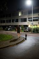 Een buurtbewoner laat zijn hond uit in Veldhuizen.